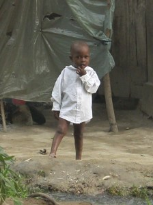 One of the children of Carrefour Poy , Haiti standing in front of his home.