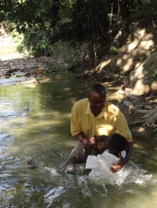 Pastor Gilbert performing baptisms in the river at Desca