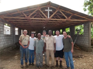 The building team standing in front of the church in Carrefour Poy with Pastors Modesir & Gilbert after completing the new roof