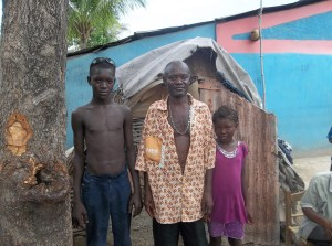 The voodoo priest with two of his children, both of whom are sponsored through The Bridge.