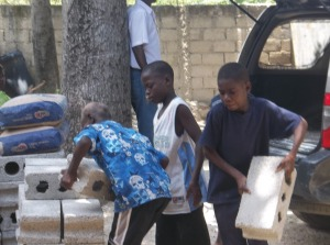 Some of the school boys unloading bricks from the back of Gilbert's car.