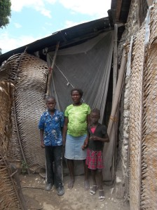 Michelet, Michelda & their mom in front of their home, July 2014.